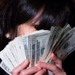 Girl hiding behind lots of money